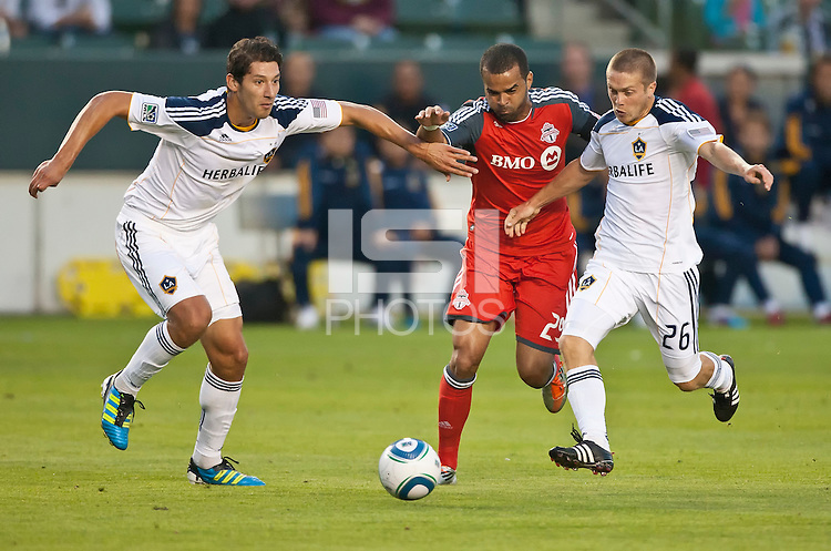 CARSON, CA – June 11, 2011: LA Galaxy defender Omar Gonzalez (4) and midfielder Michael Stephens (26) sandwich Toronto FC forward Maicon Santos (29) during the match between LA Galaxy and Toronto FC at the Home Depot Center in Carson, California. Final score LA Galaxy 2, Toronto FC 2.