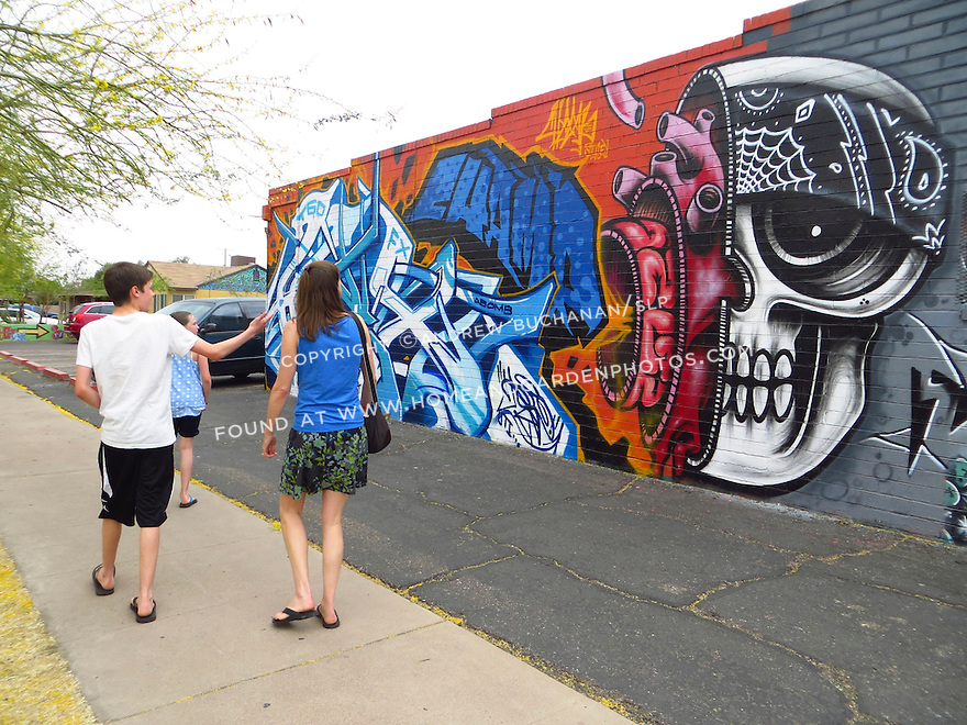 A family walks by a colorful mural on an alley wall in Phoenix.