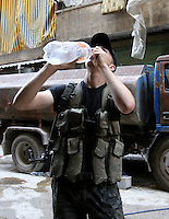 Photographer: Rick Findler..07.10.12 An exhausted soldier of the Free Syrian Army takes a refreshing sip of water between fire fights in the city of Aleppo, Syria.