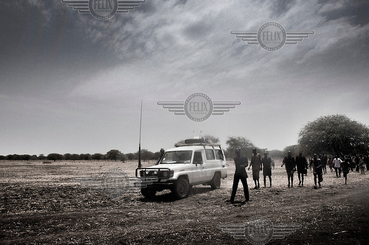 """South Sudan. 23 March 2011...Health Workers in the italian NGO """"Cuamm - Medici con l'Africa"""", installing a mobile clinic for the vaccination of children from a Dinka cattle camp.."""