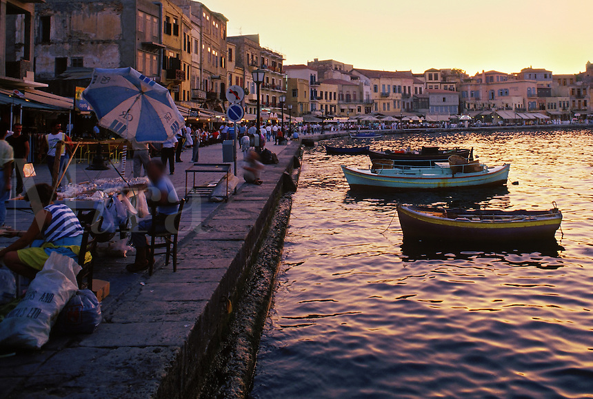 Fishing boats rest as tourists crowd to the restaurants and shops along the old quay in Hania harbor. Crete, Greece.