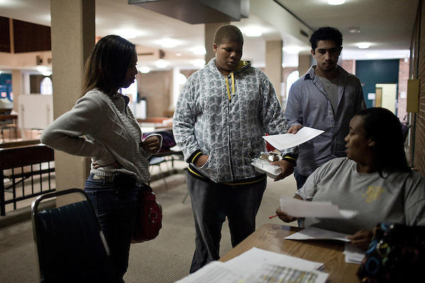 December 09, 2009. Pinehurst, North Carolina.. Students in the SandHoke Early College High School attend classes at Sandhills Community College for their last year of high school and will graduate with a high school diploma, as well as an associates degree.. Michael Smith, center, Precious Holt, left, and Jaiver Cruz, 2nd from right,  all SHECHS students, talk over the bus schedule with the driver. Smith gets up at 4:30 am to get the 6 am bus that takes the high school students on the 45 minute ride to the college.