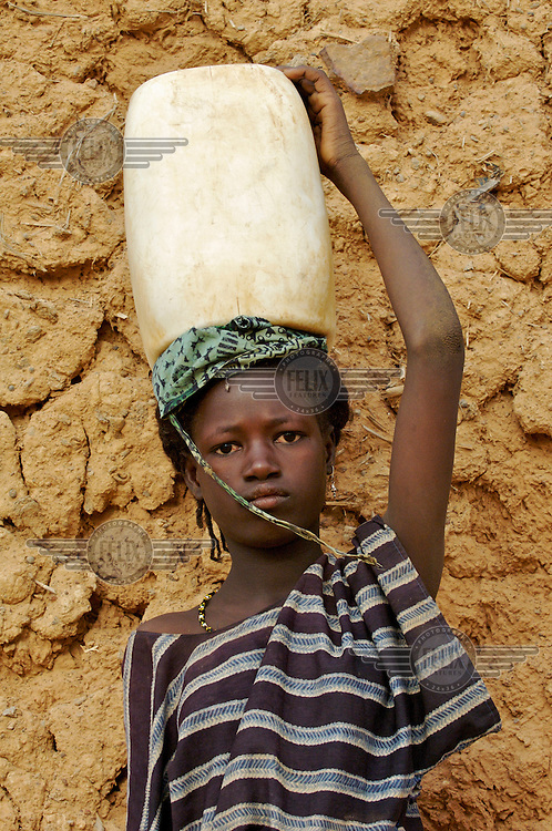 A girl carries a container of water on her head in the village of Intedeyne. /Felix Features