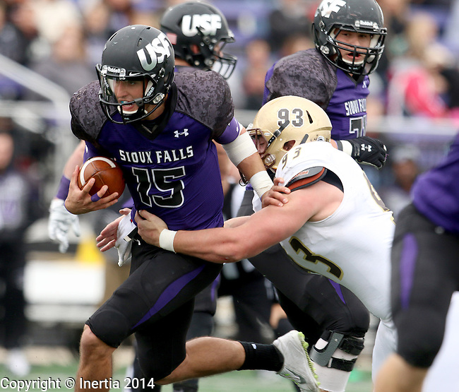 SIOUX FALLS, SD - OCTOBER 18: Luke Papilion #15 from the University of Sioux Falls tries to slip the grasp of Jacob Levtzow #93 from Southwest Minnesota State in the first half of their game Saturday afternoon at Bob Young Field in Sioux Falls. (Photo by Dave Eggen/Inertia)