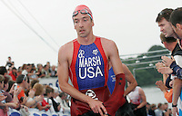 15 JUL 2007 - LORIENT, FRA - Brandon Marsh (USA) begins removing his wetsuit as he runs to T1 - World Long Distance Triathlon Championships. (PHOTO (C) NIGEL FARROW)