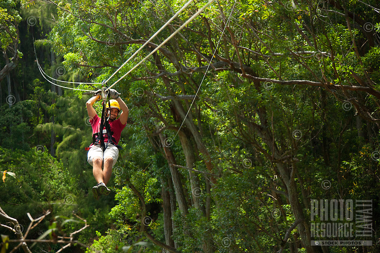 A young man flying through the canopy of trees in the rainforest while Ziplining on the Big island with Kohala zipline