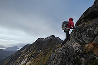 Female hiker climb steep rocky ridge towards Østhimmeltind mountain peak, Vestvågøy, Lofoten Islands, Norway