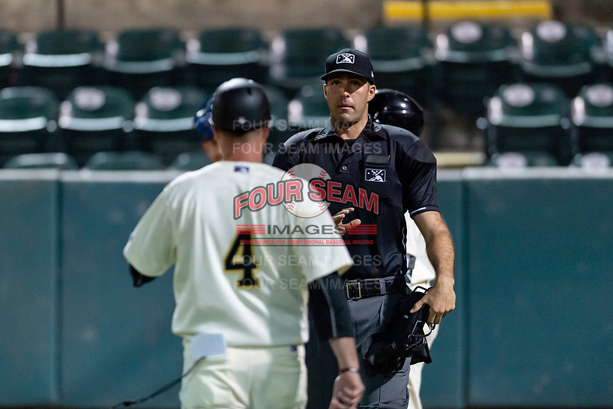 Home plate umpire Ty Kraus talks to Visalia Rawhide manager Shawn Roof (4) during a California League game against the Rancho Cucamonga Quakes at Rawhide Ballpark on April 8, 2019 in Visalia, California. Rancho Cucamonga defeated Visalia 4-1. (Zachary Lucy/Four Seam Images)