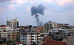 Smoke rises above buildings during an Israeli air strike on Gaza City on July 20 2018. Photo by Dawoud Abo Alkas
