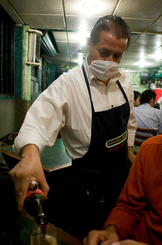 Bartenders and waiters wear masls during the Swine Flu outbreak. Cerveceria el Pierrot Calle 17 in San Pedro los Pinos. Bike rides around Mexico City at night with Luis Mdahuar, Mike Smith, and Kurt Hollander (during the swine flu pandemic).  Mexico DF May 6, 2009