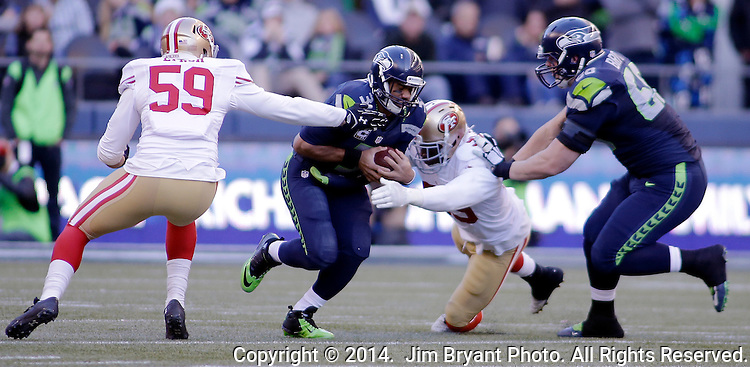 Seattle Seahawks quarterback Russell Wilson ( 3), get sacked by San Francisco 49ers linebacker's Aaron Lynch (59) and Aldon Smith (99) as Seahawks guard Justin Britt blocks at CenturyLink Field in Seattle, Washington on December 14, 2014.  The Seahawks beat the 49ers 17-7.    © 2014. Jim Bryant Photo. All Rights Reserved.