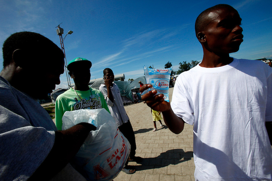 Nov 10, 2010 - Port-au-Prince, Haiti.Local residents of the Cite Soleil area of Port-au-Prince, Haiti purchase small bags of water from a street vendor inside a tent city on Wednesday, November 10, 2010 as fears of a Cholera outbreak spread through the area just two days after cases of the infection were confirmed in the area, the poorest slum in Haiti's capital. Officials from the Pan American Health Organization warn that Haiti's cholera epidemic, spread primarily through consuming infected water and food, is likely to grow much larger in the wake of Hurricane Tomas.  (Credit Image: Brian Blanco/ZUMA Press)