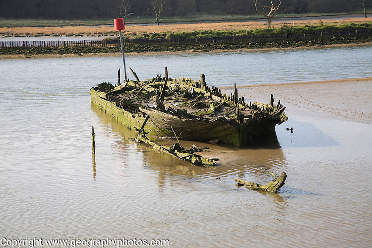 Abandoned sunk old wooden boat on sandbank in the River Deben at Melton, Suffolk, England