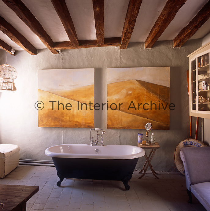 A bathroom with an exposed beam ceiling and stone tiled floor. Two complimentary artworks hang above a free-standing roll top bath.