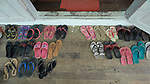 Sandals are arranged outside the entry to a school classroom in Kalay, a town in Myanmar. Students take off their footwear as they enter class.