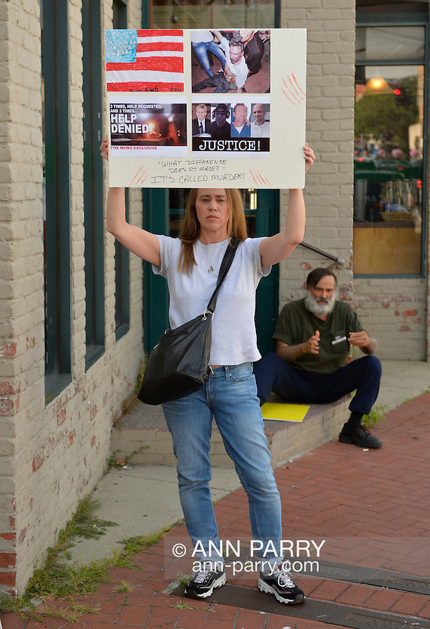 """Huntington, New York, U.S. - August 6, 2014 - A protestor holds a sign with """"3 times help requested, 3 times help denied"""" about the bombing in Benghazi that resulted in death of U.S. Ambassador Stevens and 3 other Americans, as she stand outside the Book Revue where H. Clinton will have a book signing for her new memoir, Hard Choices at 6pm. Clinton's book is about her four years as America's 67th Secretary of State and how they influence her view of the future."""