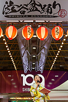 An emcee, wearing a kimono, talks as people enjoy dancing and watching the third Annual Shibuya Bon Odori festival, Bon dancing is a Japanese custom at summer matsuri or festivals all over Japan. The Shibuya Bon Odori takes place in front of the iconic Shibuya 109 building. Shibuya, Tokyo, Japan. Sunday August 4th 2019