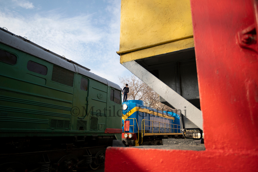 Uzbekistan - Tashkent - A young boy stands on top of an old Soviet locomotive located at the Railway Museum.