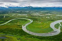 Aerial view of a river winding through the tundra on the Alaska Peninsula, Alaska's southwest coast. Aleutian mountain range in the distance.