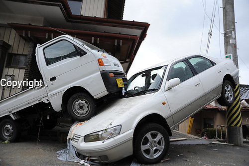 A passenger car sits sandwiched between a pickup truck and a light pole following an 8.9-magnitude earthquake, which triggered a devastating tsunami through this Japanese coastal city.