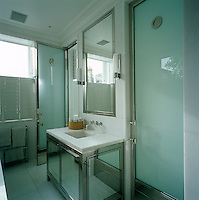 The bathroom has a mirrored cupboard under the basin and frosted glass doors leading to the walk-in shower and sauna respectively