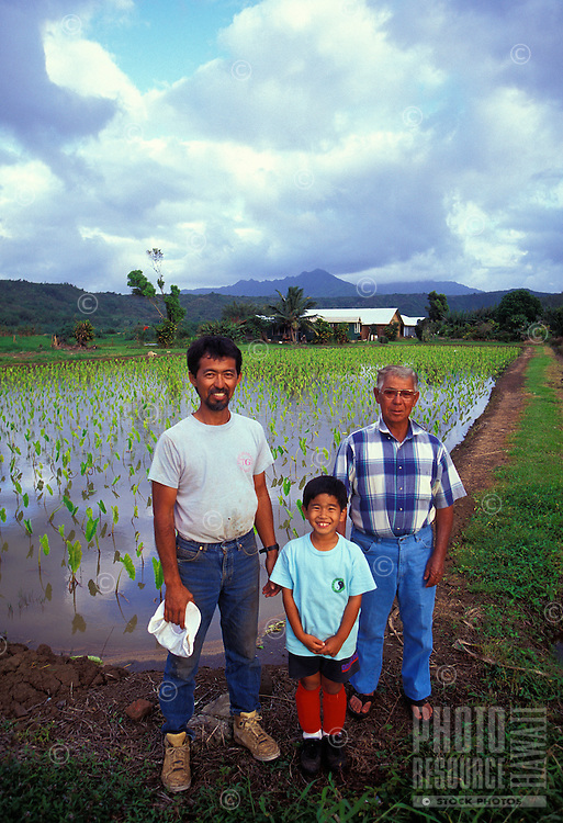 Three generations of the Haraguchi family standing in front of a loi (taro pond) on their farm in Hanalei, Island of Kauai