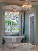 Walker Zanger glass tiles in a classic Moroccan pattern surround the soaking tub with a Nina Campbell tropical floral print fabric for the drapery and tufted bench
