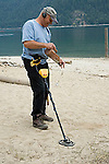 Man searching for coins with metal detector