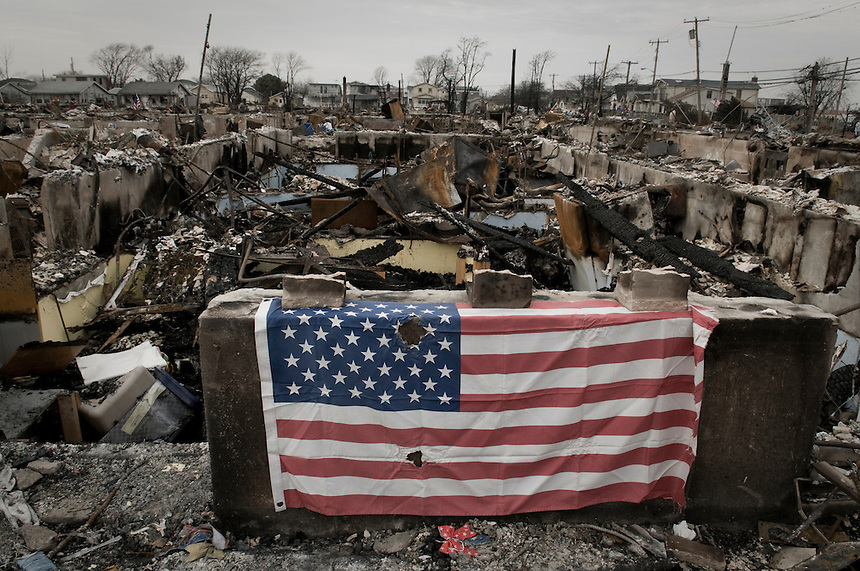 An American flag adorns the ruins of one of the 101 burned houses in Breezy Point, NY, when Hurricane Sandy hit the area.