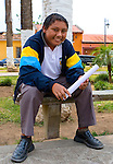 Smiling Guatemalan boy sits in park during school break in Antigua, Guatemala