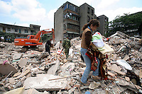 Residents look for belongings and signs of life at a site where 2 apartment buildings collapsed in Mianzu, Sichuan, China. Rescue workers have given up on finding people still alive and began to use heavy machinery..14 May 2008