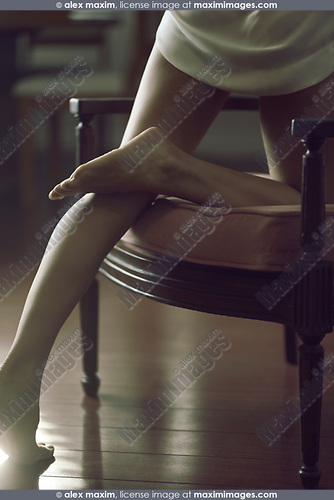 Bare legs of a young woman leaning on a chair, sensual romantic closeup