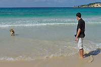 Man (18) with dog contemplating ocean from beach, Punta Cana, Dominican Republic