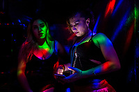 A Salvadoran sex worker looks at the phone screen while talking with her co-worker in a sex club in San Salvador, El Salvador, 25 November 2018. Sex workers' task in the club is to be an entertaining and seductive companion. Performing erotic dance on the pole they make the customers stay as long as possible and buy relatively expensive alcoholic beverages from which they have a certain share. Sex workers are not obliged to have sexual intercourse with the club customers, they decide themselves, usually according to their current economic situation.
