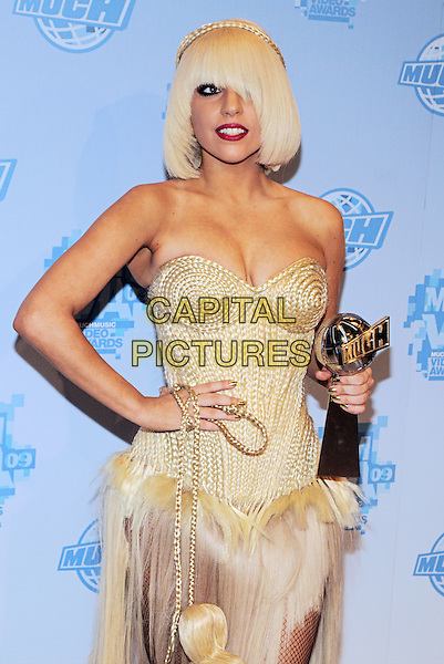 LADY GAGA (Joanne Stefani Germanotta) .Lady Gaga attends the 20th Annual MuchMusic Video Awards at the MuchMusic HQ, Toronto, Ontario, Canada..June 21st, 2009.half length gold beads beaded pearls yellow cream strapless top corset bustier dress feather fur bag purse fishnet stockings award trophy bag purse hand on hip cleavage red lipstick braid plait.CAP/ADM/BPC.©Brent Perniac/AdMedia/Capital Pictures.