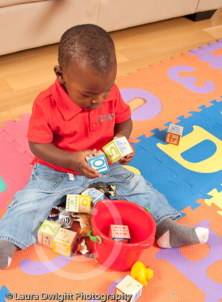 12 month old baby boy sitting on floor banging two square blocks together vertical