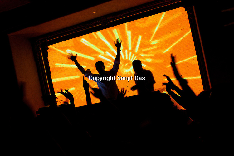 Guests riase hands while dancing to the DJ's music in The club LAP located in Hotel Samrat in New Delhi, India. Photograph: Sanjit Das/Panos