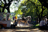 Porto Alegre, Brazil. Farroupliha park; park policeman on horseback with snack kiosk and vendor. Rio Grande do Sul State.