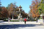 People walking by monument fountain in El Retiro park, Madrid, Spain