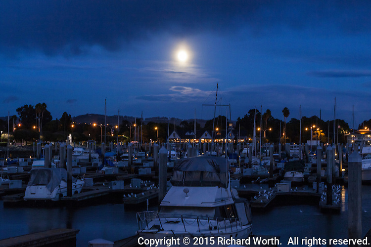 What will be the Full Cold Moon in ten hours rises and shines through the clouds on the boats moored at the San Leandro Marina on San Francisco Bay.