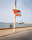 ERITREA, Massawa, two men walk along the waterfront towards the Port of Massawa by the Red Sea