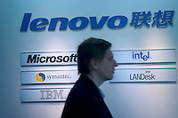 A western journalist walks past Logos of Lenovo and IBM, Microsoft,Intel,Symantec and  LANDesk at Lenovo Innovation Center in Beijing, China..