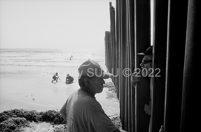 Tijuana, Mexico<br /> August 18, 2007<br /> <br /> The Mexican US border fence dives into the sea on a beach. The beach is split in two by the barrier. The US side is only open to the public on the weekends and people come out to talk with Mexicans through the fence. ..The Mexican beach is always full of life while the US beach is often deserted. Music, children, food, and vendors cover the beach. Mexicans pass back and forth playfully through the barrier under the watchful eye of a border patrolman not far away.<br /> <br /> Signs on the US side warn of the polluted waters that the US says comes from a waste treatment plant on the Mexican side.