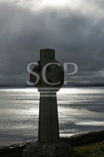 Ireland. Celtic cross by the sea in afternoon sun. Moody.