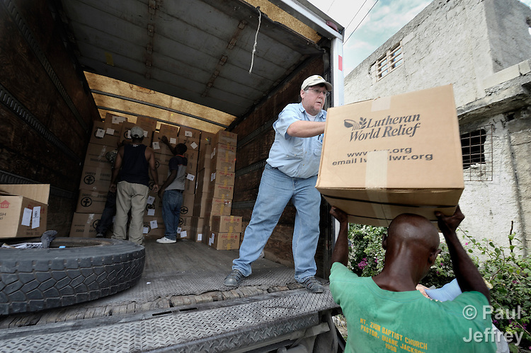 In Port-au-Prince, Don Tatlock (center), an emergency worker for Church World Service, a member of the ACT Alliance, unloads relief material from Lutheran World Relief, also an ACT Alliance member, brought into earthquake-ravaged Haiti from the Dominican Republic on January 25.
