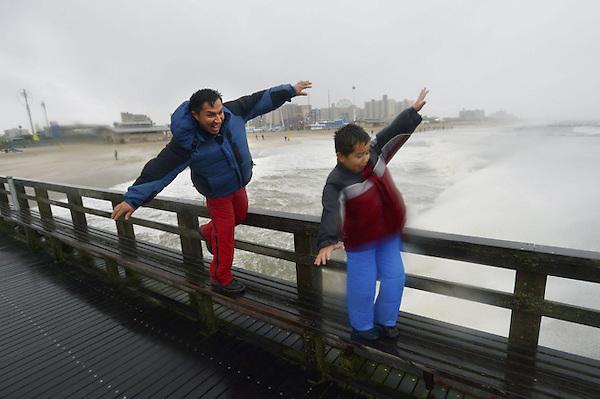 """JLX28. NUEVA YORK (ESTADOS UNIDOS), 29/10/2012.- Un hombre y su hijo juegan a desafiar al viento, en Nueva York, Estados Unidos, hoy, lunes 29 de octubre de 2012. El huracán """"Sandy"""" se encuentra a 180 kilómetros en el sudeste de Atlantic City, en Nueva Jersey, donde tocará tierra """"pronto esta tarde"""", advirtió hoy el Centro Nacional de Huracanes (CNH) de EE.UU. EFE/Justin Lane"""