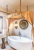 ZANZIBAR, a gold canopy over a white bathtub in Baraza Hotel