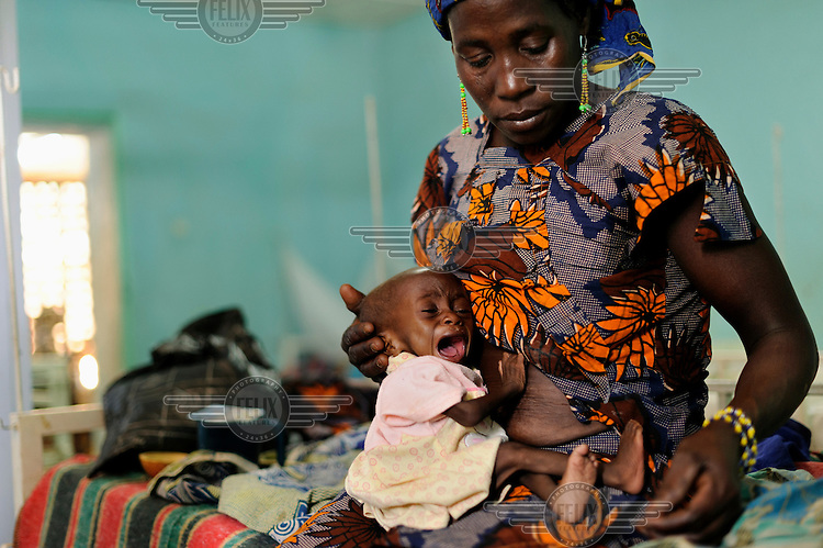 One year old Houzeima Mani cries as she sits on her mother's lap at a Save the Children stabilisation centre in Matamey, where she is being treated for severe malnutrition. Her mother, Maria Abdou, says Houzeima is her only surviving child; seven others have died.