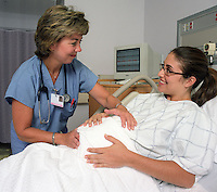 A pregnant woman receives attention from medical staff in hospital delivery room.