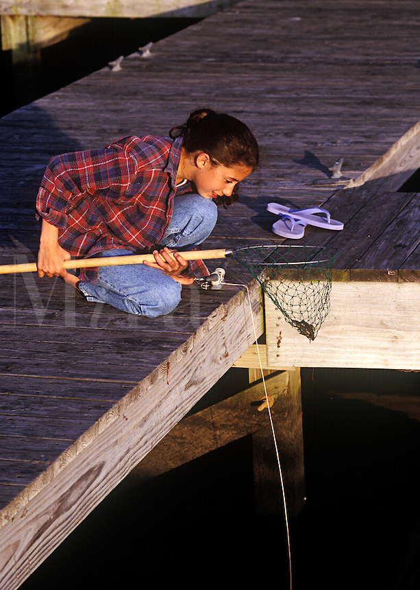Young girl catching crabs from a dock.